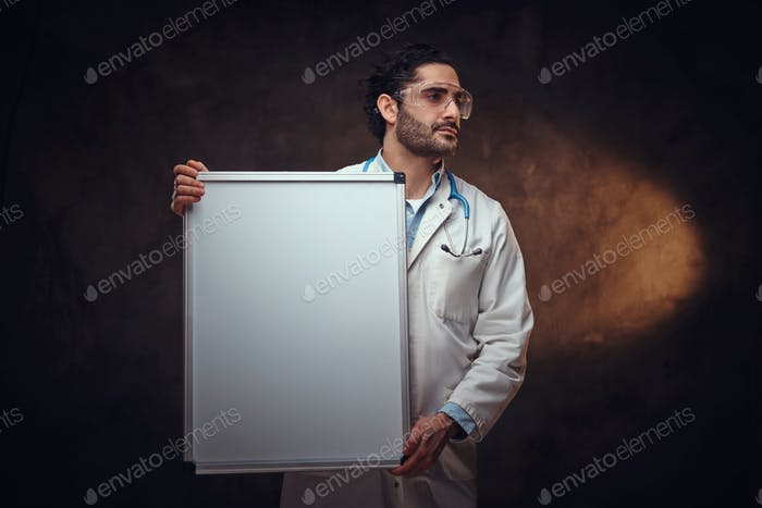 Handsome medic with white board in hands