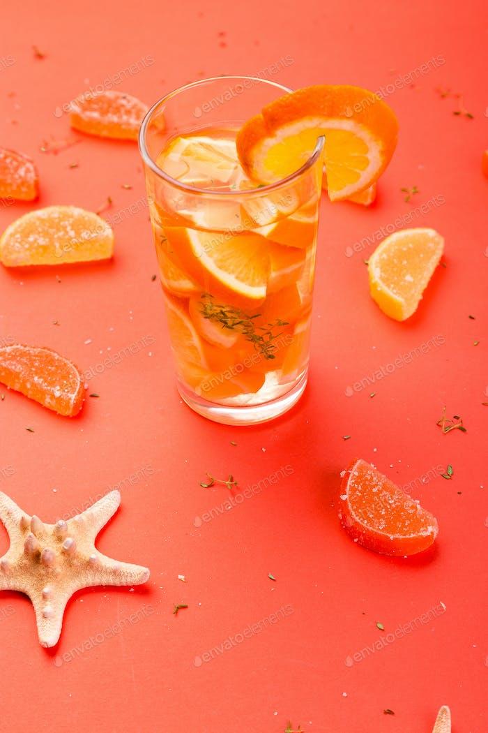 Orangenfruchtcocktail, Entgiftungswasser auf orangefarbenem Hintergrund.