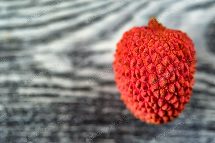 Single lychee on wooden background close