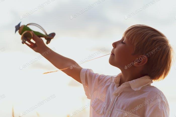 Junge in einem weißen Hemd mit einem Flugzeug in Händen gegen den Himmel.