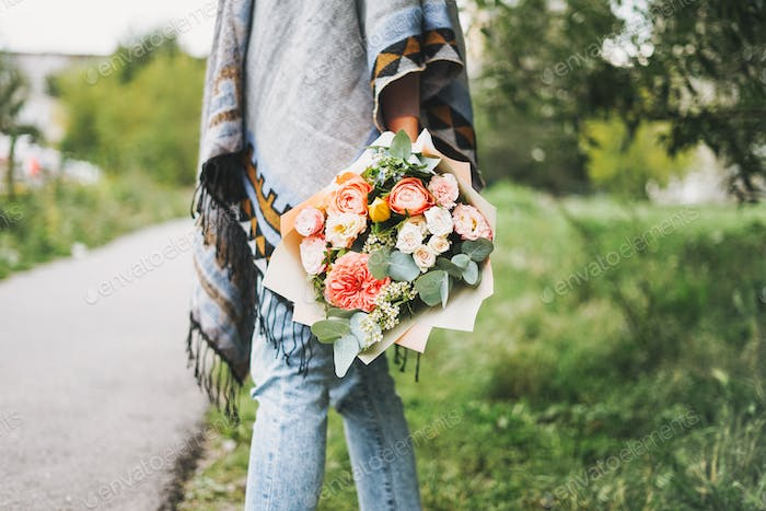 Young woman in poncho and jeans holds beautiful bouquet of different flowers