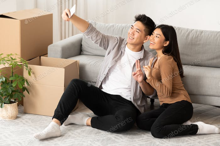 Asian man and woman taking selfie sitting on the floor