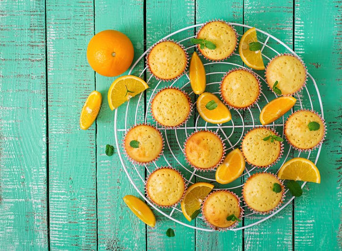 Tasty muffins with oranges and mint. Top view