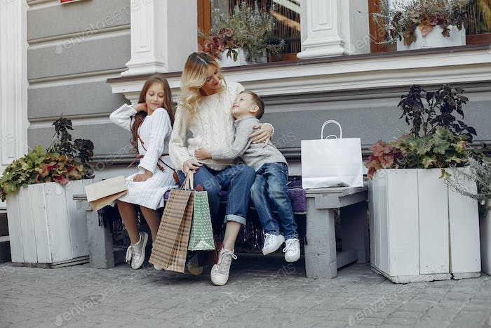 Mother with child with shopping bag in a city