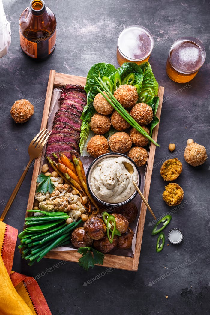 Arabian style dinner: falafel, beef, babaghanoush, bean, green peas and roots vegs. Top view.
