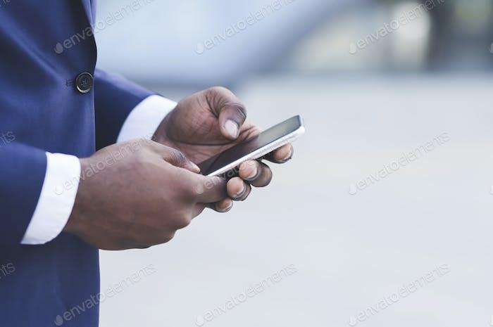 Afro Geschäftsmann Hände mit Smartphone in Stadt, Nahaufnahme