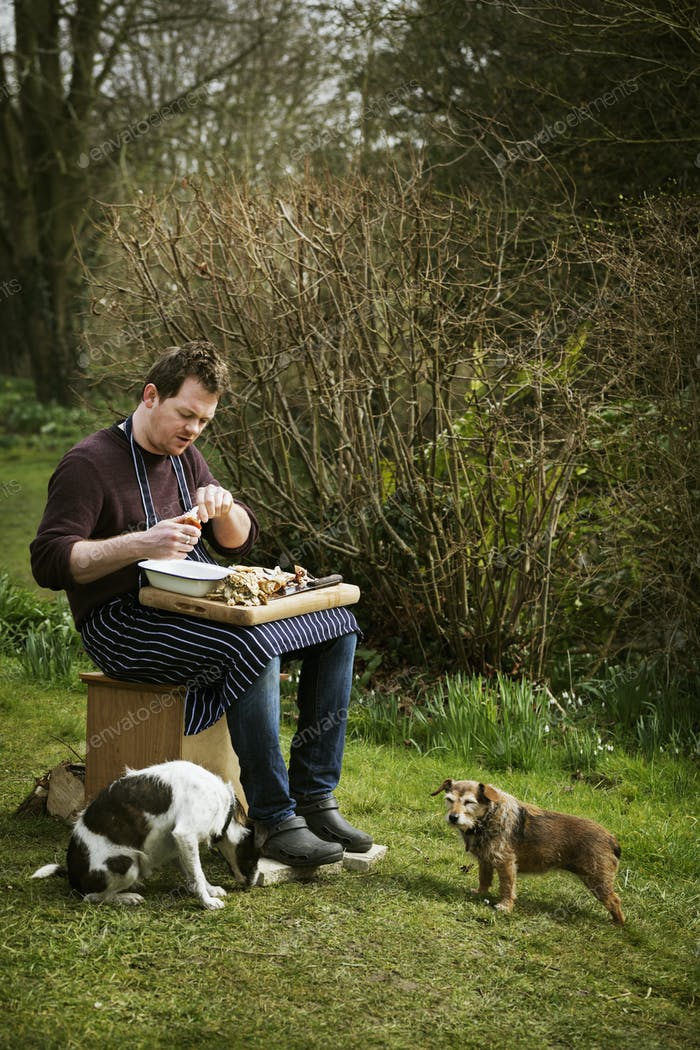 Chef sitting outdoors, preparing seafood, two dogs at his feet.