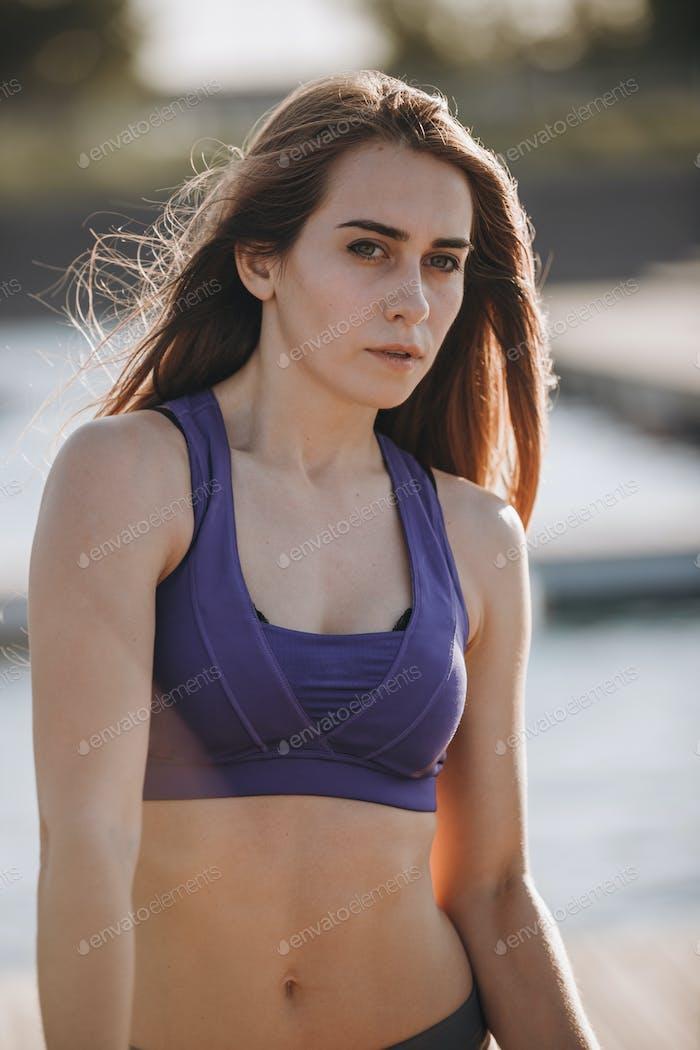 Chica joven delgada con pelo largo castaño en una parte superior deportiva