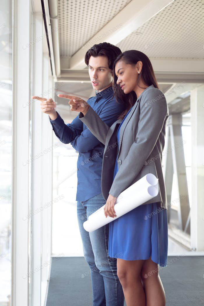 Side view of diverse male and female architects interacting with each other in office