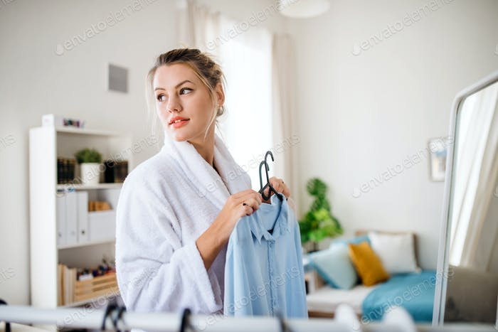 Young woman indoors at home in the morning, choosing clothes to wear.