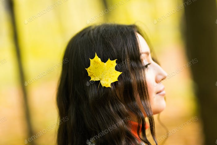 beautiful girl with maple leaves in her hair