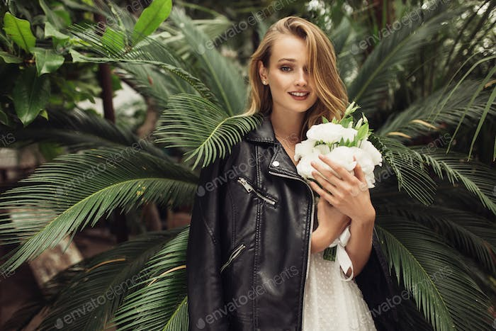 Young pretty smiling woman in white dress with black leather jac