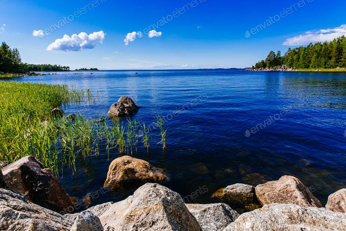 Clear water blue lake with stones and green forest on a sunny summer day in Finland.