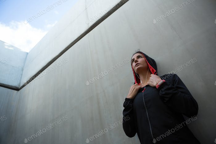 Fit woman leaning on wall
