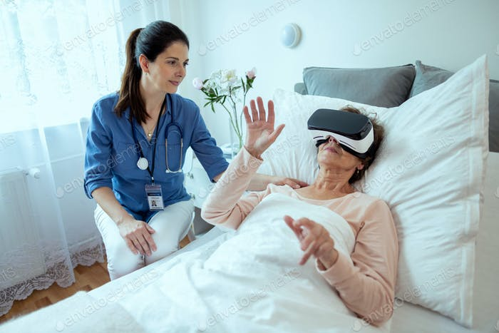 Female Doctor Checking on Elderly Patient Lying in Hospital Bed Doing Therapy Via VR Technology.