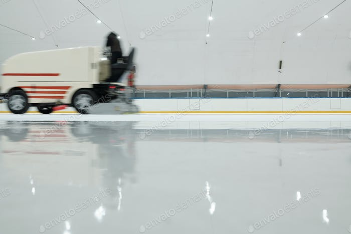 Special lorry or ice flattening machine moving along ice-rink at leisure center