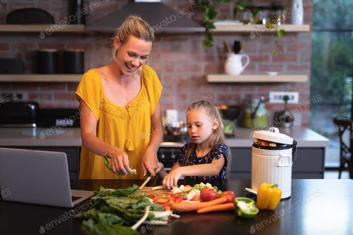 Caucasian woman and her daughter spending time in the kitchen and using a laptop
