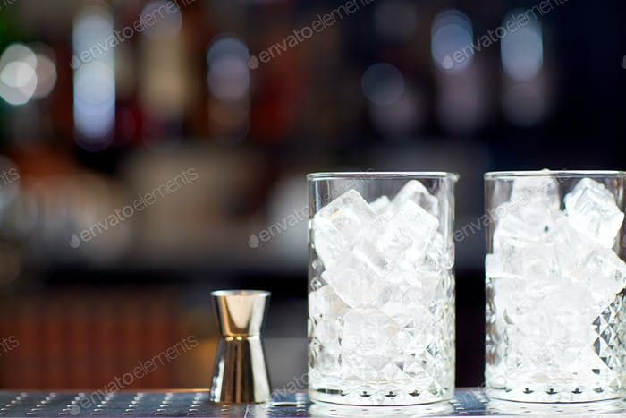 glasses with ice and jigger on bar counter