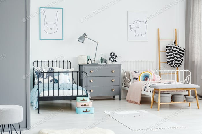 White bed for a girl and black one for a boy in a siblings bedro