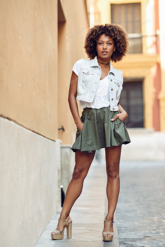 Young black girl, afro hairstyle, standing in urban background