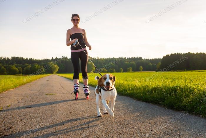Patinaje niña con perro Beagle al aire libre en la naturaleza