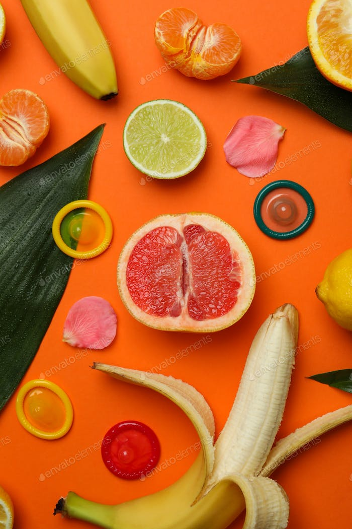 Sex concept with fruits and condoms on orange background