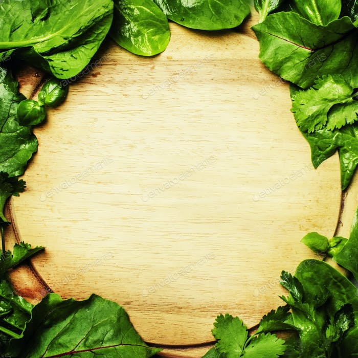 Food background, wooden cutting board in a frame of green leaves