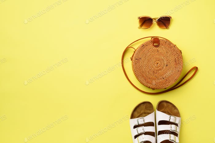 Stylish rattan bag, birkenstocks, sunglasses on yellow background. Top view with copy space. Trendy