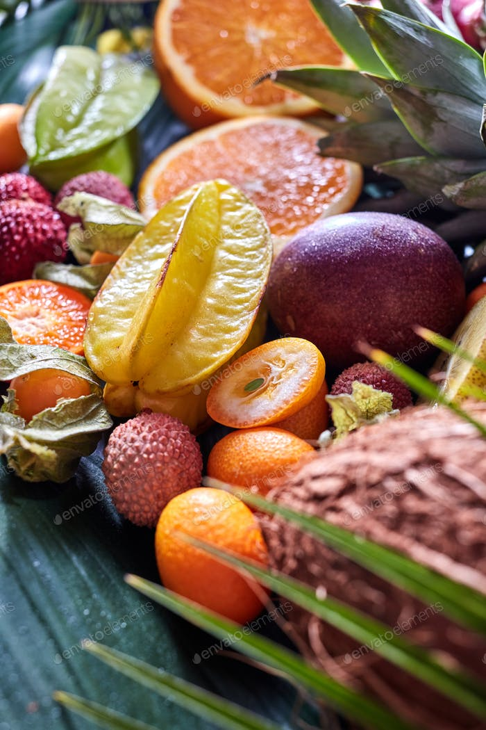 Summer exotic fruits - carambola, pineapple, coconut, mango, kiwi, halves of orange on a green