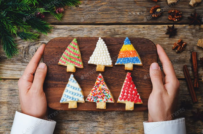 Men's hands holding colored Christmas tree cookies