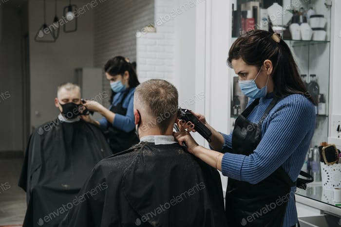 Barber shops, hair salons shutting down, second lockdown. Hairdresser in face mask peeling and