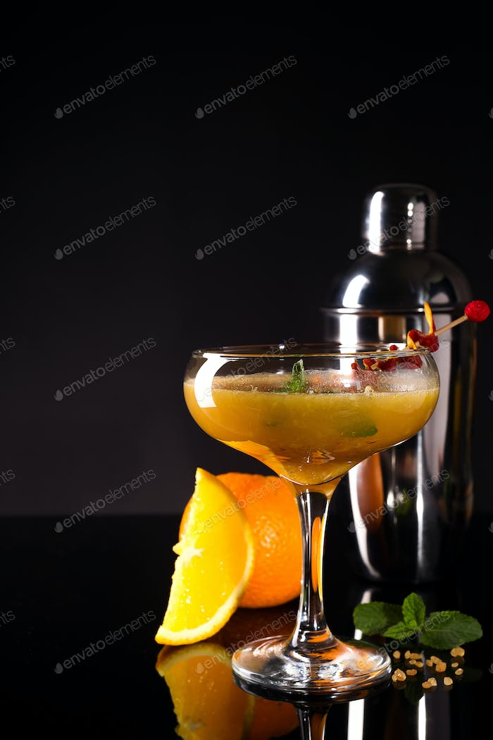 Glass of the orange alcoholic drink with ice and slice of orange peel on the dark background