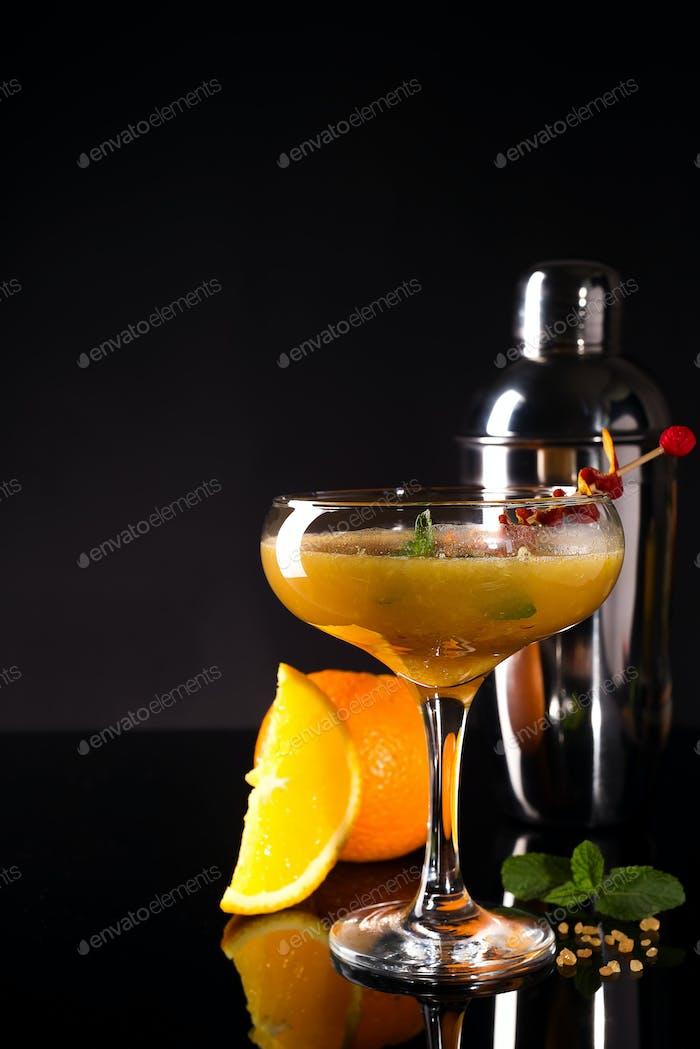 Glass of the orange alcoholic drink with ice and slice of orange peel on the dark background