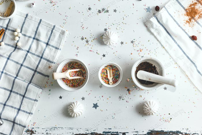 Three saucer with candy sprinkles, surrounded by sweets. Top View