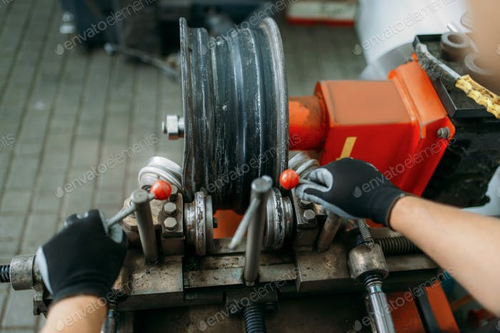 Mechanic works with wheel on disc rolling machine