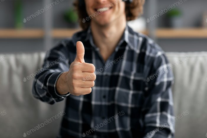 Guy Gesturing Thumbs-Up Approving Something Sitting At Home, Cropped