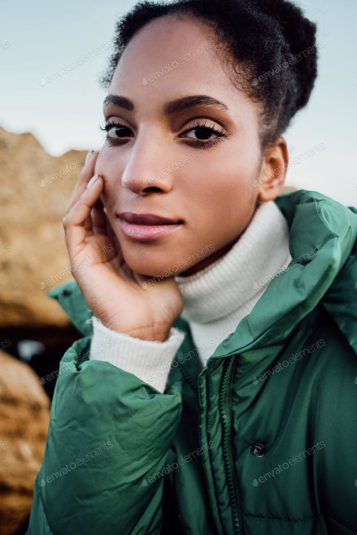 Close up beautiful African American girl in down jacket dreamily looking in camera outdoor