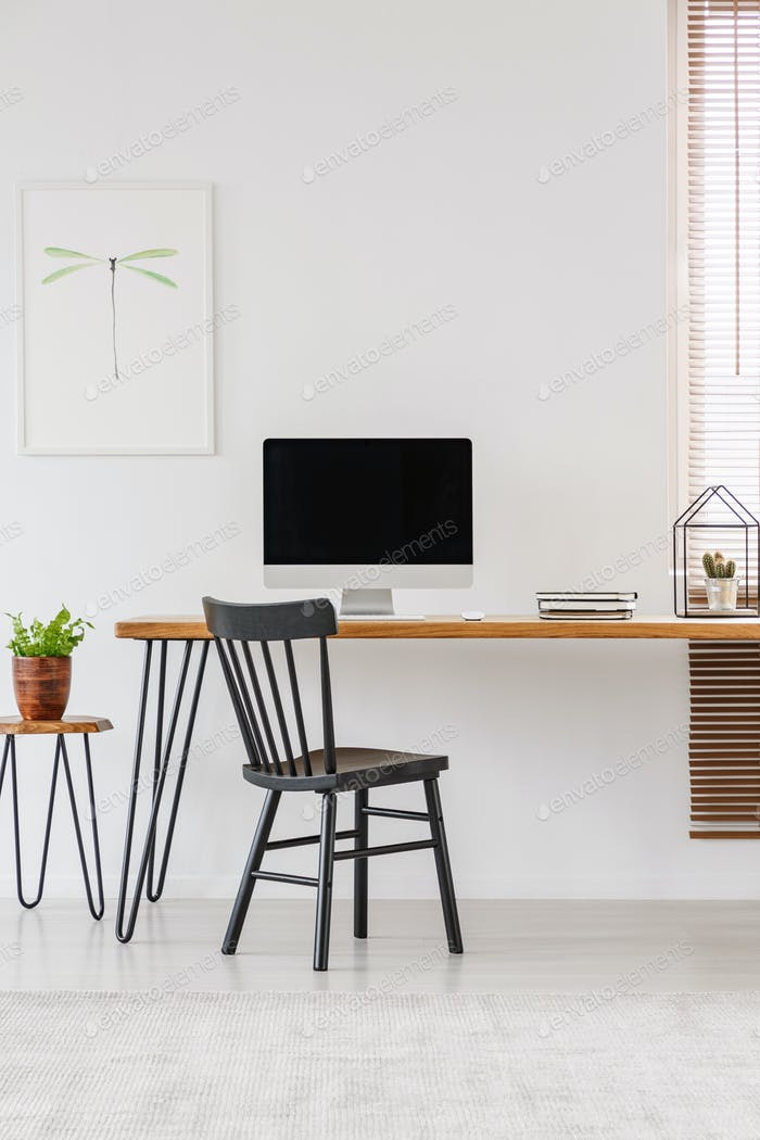 Simple interior of a home office with black chair standing at a