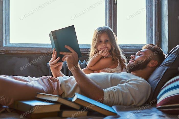 Schöner junger Vater Lesen Märchenbuch seine kleine Tochter auf dem Bett.