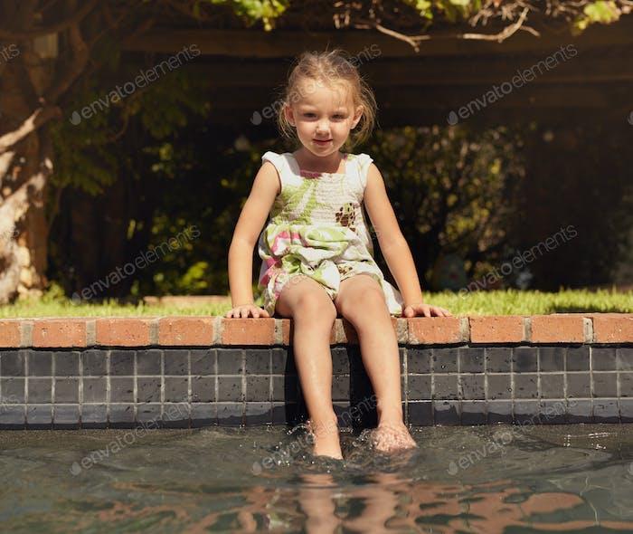 Liebenswert kleines Mädchen genießen sitzen durch Rand der pool