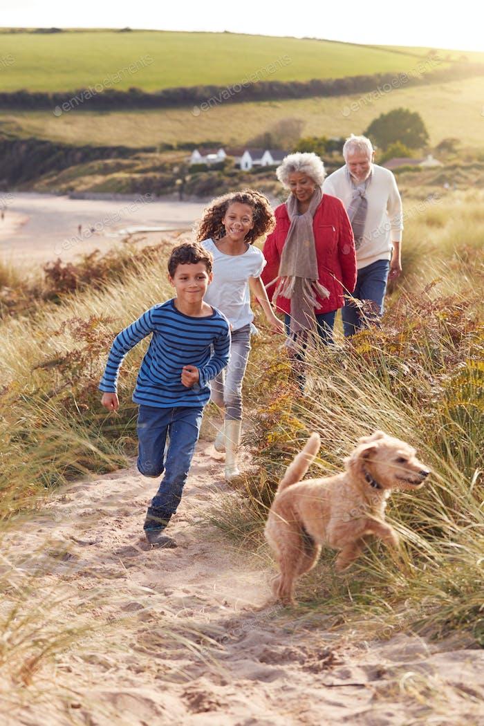 Enkelkinder und Haustier Hund Erkundung Sand Dünen Mit Großeltern Auf Winter Strand Urlaub