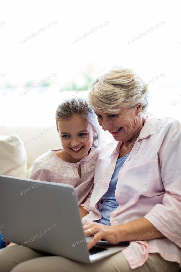 Granddaughter and grandmother using laptop
