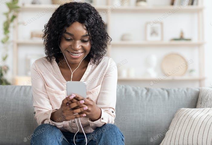Inländische Zeitvertreib. Entspannte Afroamerikanisches Mädchen Musik mit Smartphone und Ohrhörern
