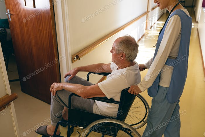 Female nurse pushing disabled senior male patient sitting in wheelchair at retirement home
