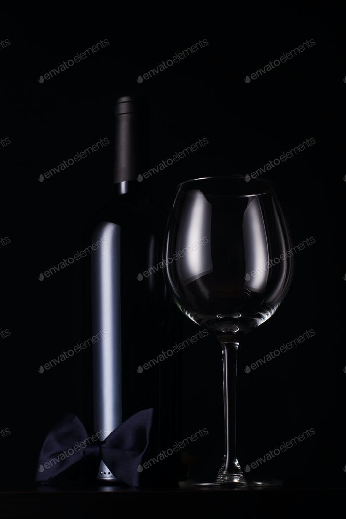black red wine bottle with empty tall glass