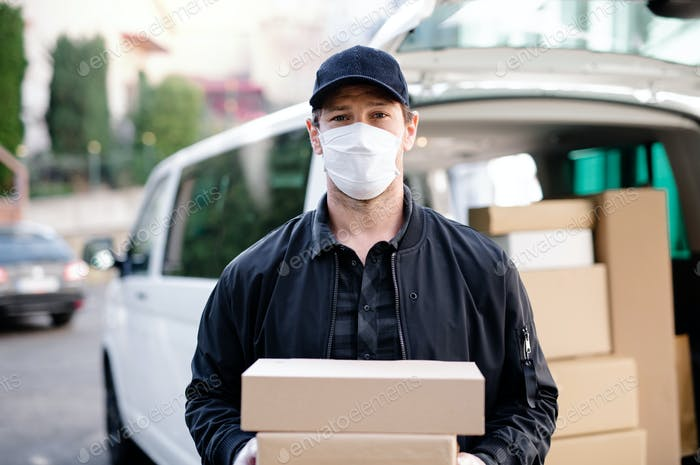 Delivery man courier with face mask delivering parcel boxes in town