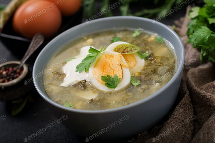 Green soup of sorrel in blue bowl.