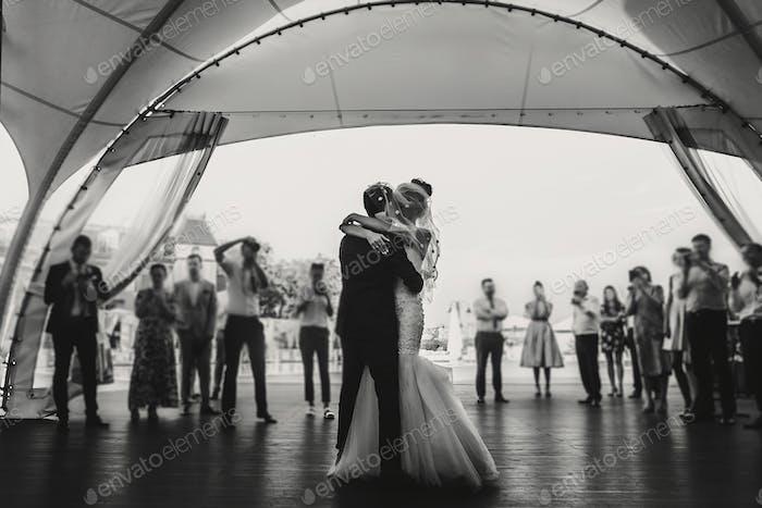 Stylish happy bride and groom gently dancing at wedding reception
