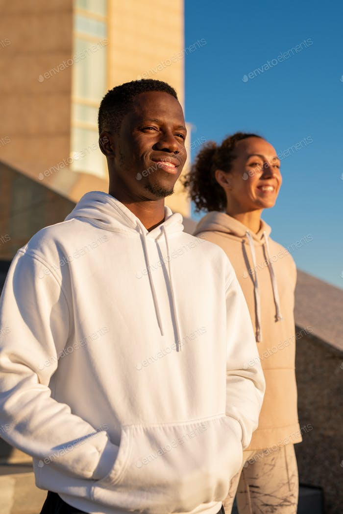 Young African sportsman and his girlfriend of Caucasian ethnicity in hoodies