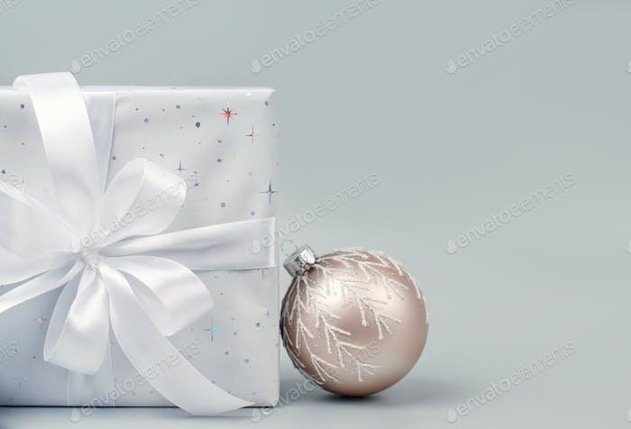 Weihnachtsgeschenk und cremefarbene Weihnachtskugel